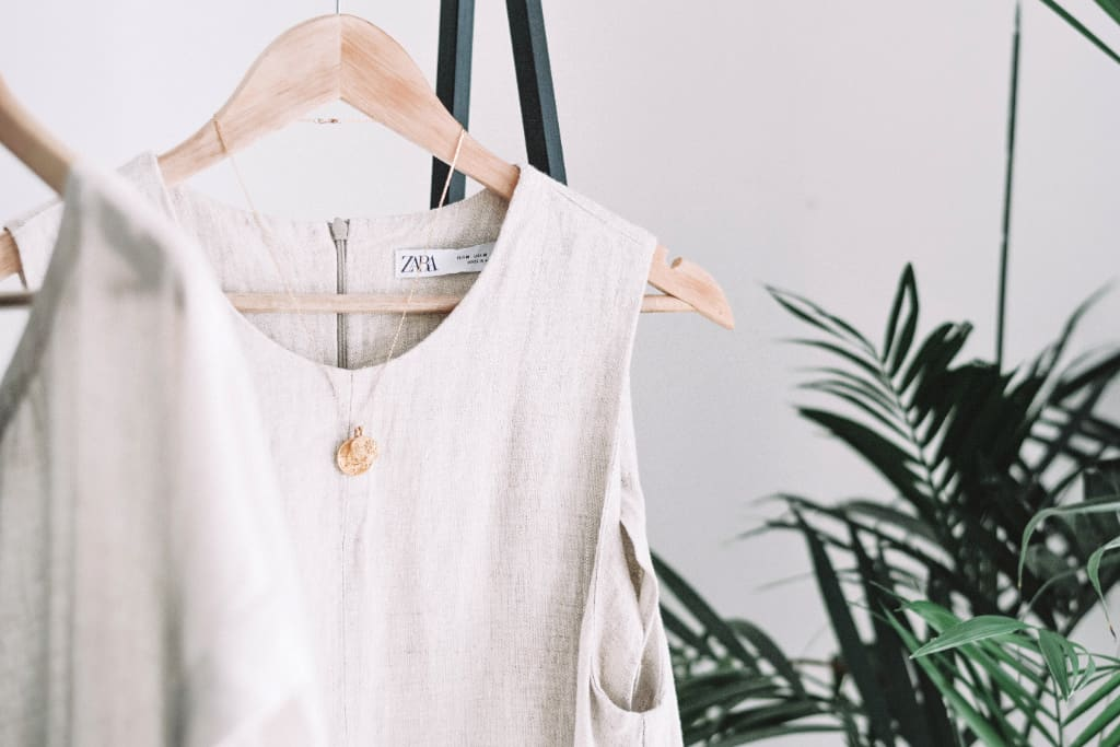 A capsule wardrobe with white linen shirt hanging there