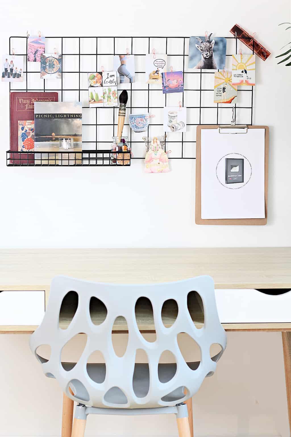 A minimalist office wall grid dream board with blue chair