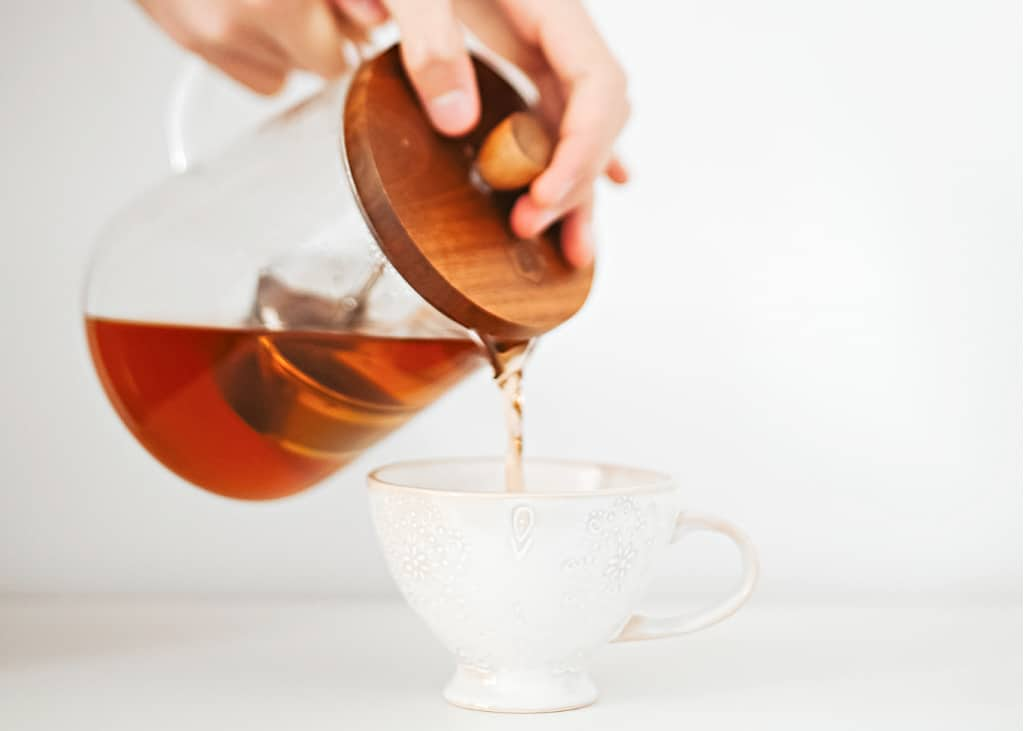A woman pouring tea as part of intentional living practice