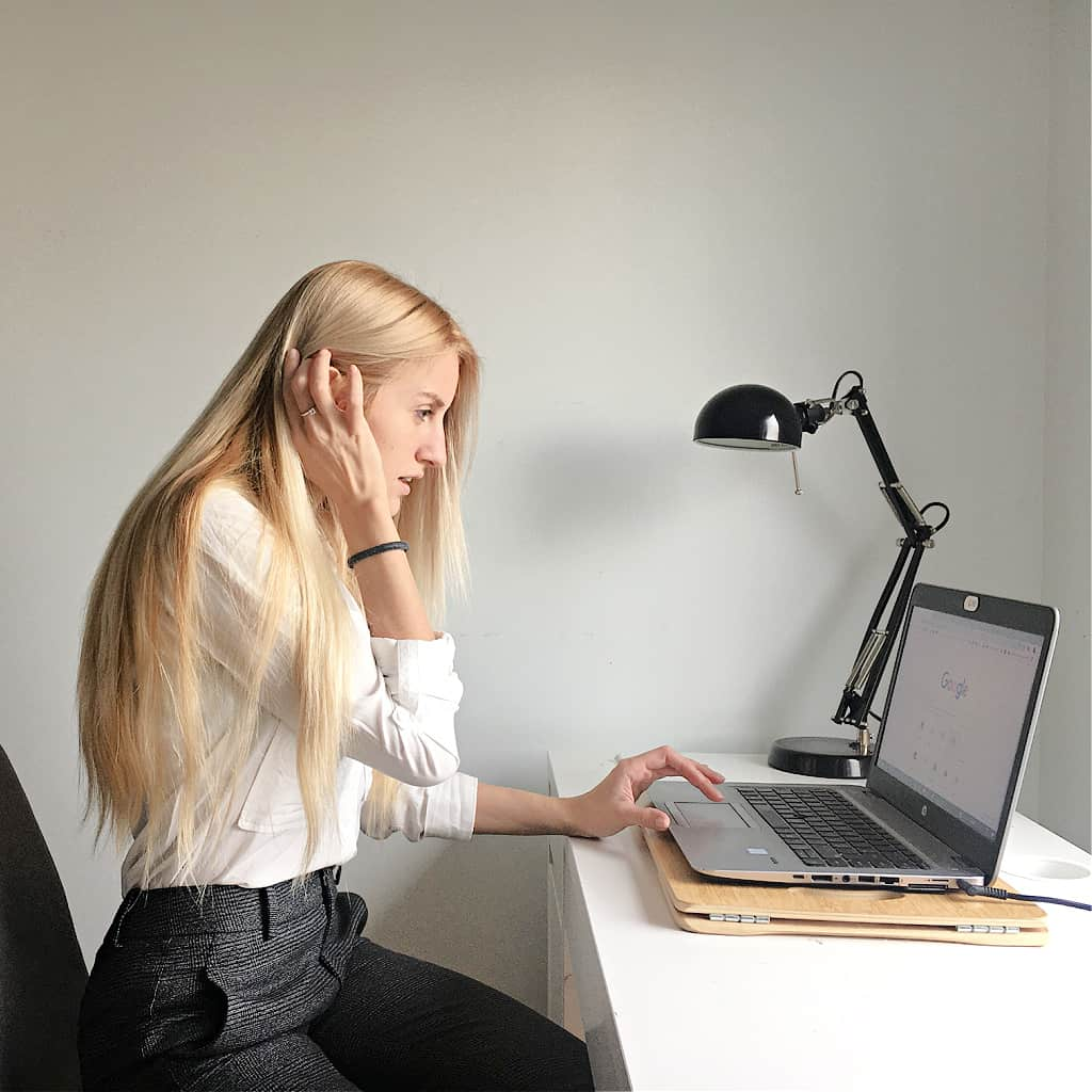 A woman feeling overwhelmed and looking up how to stop the stress online