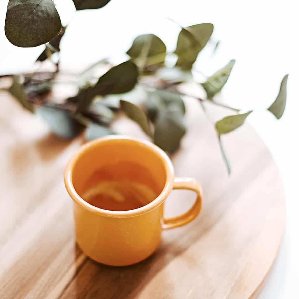 A minimalist cup of tea on a wood platter