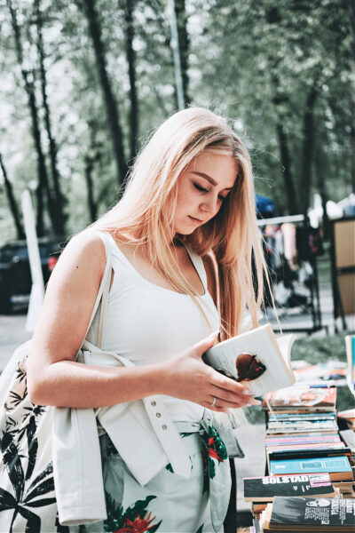 A woman using good minimalist shopping habits to save money on a book