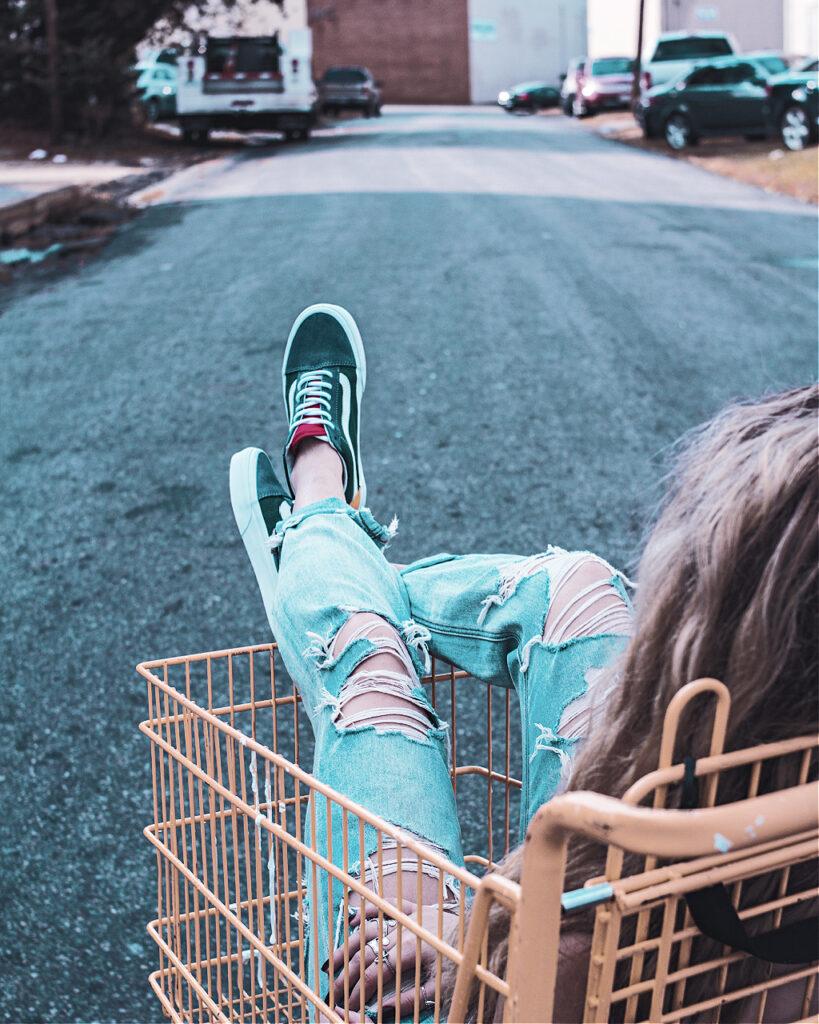 A woman in a shopping cart regretting not shopping like a minimlalist